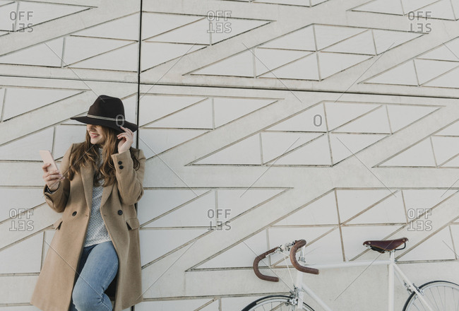 Young hipster woman near to a bicycle holding a phone