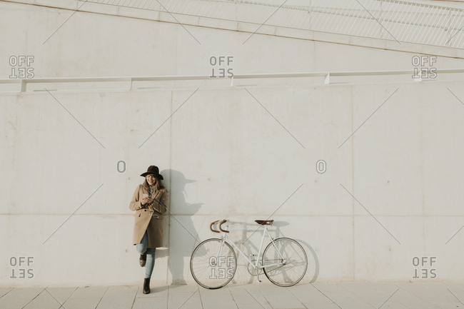 Young hipster woman leaning next to a bicycle- holding a phone