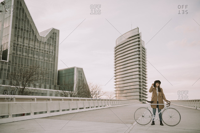 Young hipster woman with a bicycle on bridge in the city