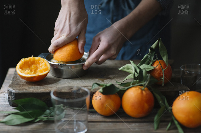 Young man's hands squeezing orange