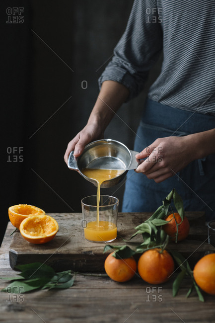 Young man pouring freshly squeezed orange juice into a glass- partial view