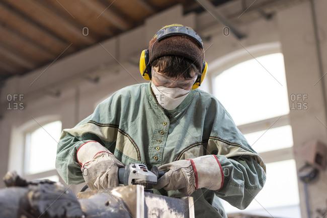 Art foundry- Female foundry worker polishing metal