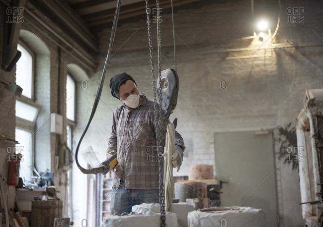 Art foundry- Foundry worker lifting casting mould