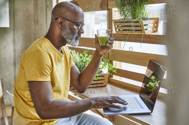 Mature businessman with smoothie using laptop at the window in office