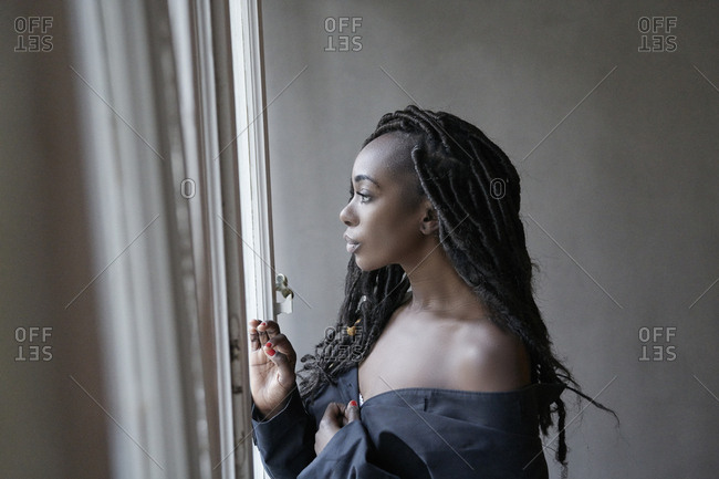 Profile of woman with dreadlocks looking out of window