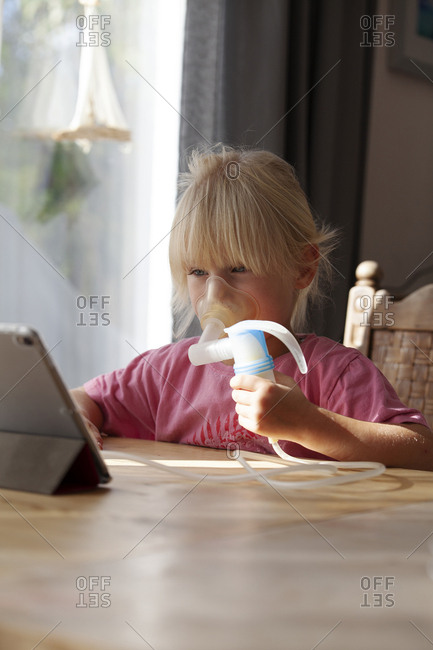 Portrait of blond little girl using asthma inhaler while looking at digital tablet