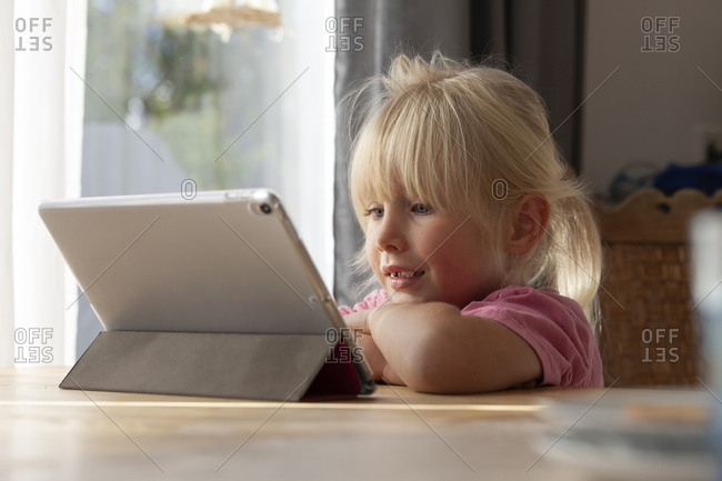 Portrait of blond little girl using digital tablet at home