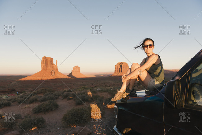 USA- Utah- Monument Valley- Woman sitting on car bonnet- enjoying the sunset in Monument Valley