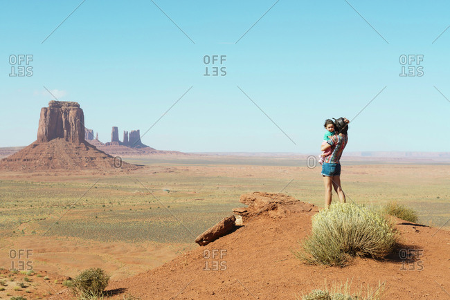 USA- Utah- Monument Valley- Mother traveling with baby girl- mother carrying girl- standing on viewpoint