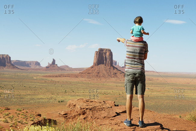 USA- Utah- Monument Valley- Father traveling with baby- girl on shoulders and pointing to Monument Valley landscape