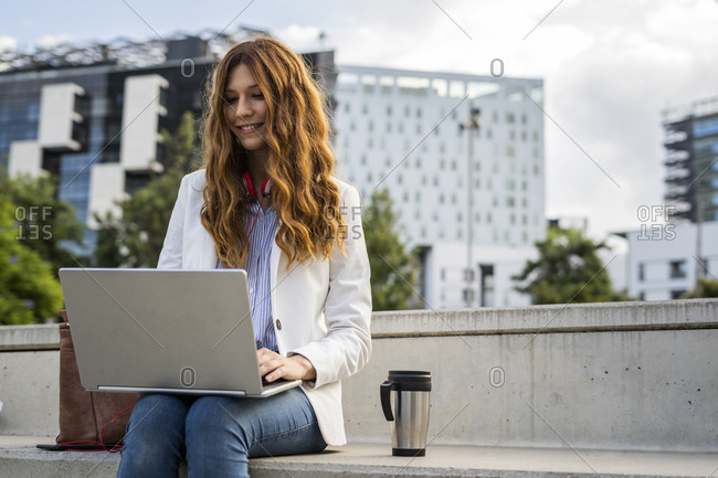 Young businesswoman sitting on stairs in the city- working with laptop