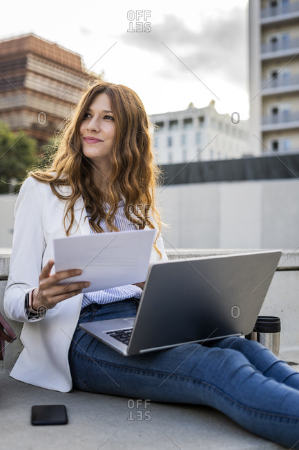 Young businesswoman sitting on stairs in the city- working with laptop- holding document