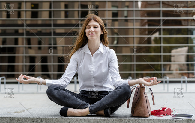 Businesswoman sitting cross-legged on pavement- meditating