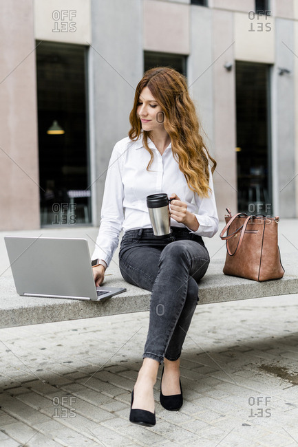 Young businesswoman sitting on bench in the city- working with laptop- drinking coffee