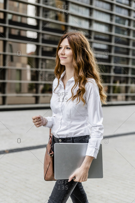 Young businesswoman walking in the city- carrying laptop