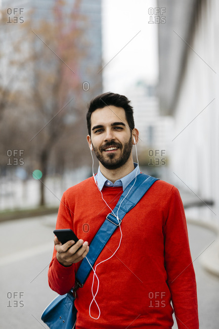 Casual businessman commuting in the city- using earphones and smartphone