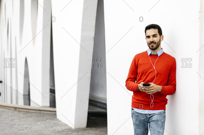 Casual businessman leaning on wall- using earphones and smartphone