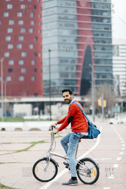 Casual businessman commuting in the city- using his folding bike