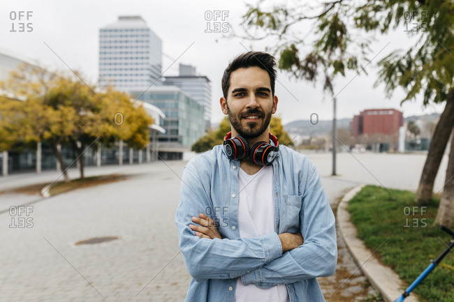 Man with headphones standing in the city- with arms crossed