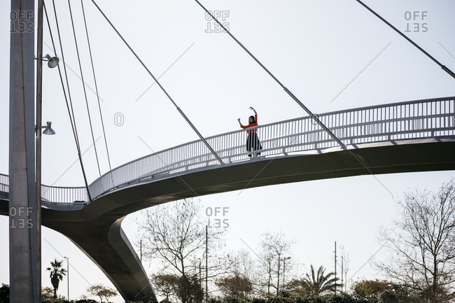 Young contemporary dancer practicing on a footbridge