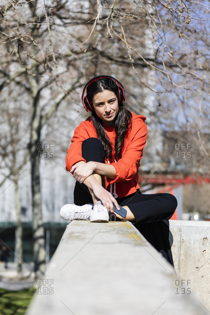 Young contemporary dancer wearing red hoodie shirt- sitting and listening to music
