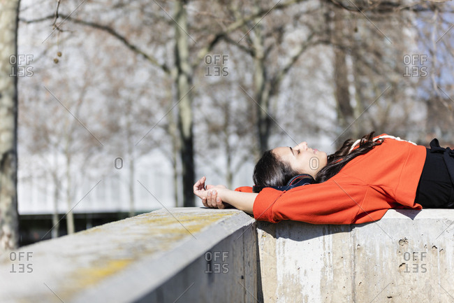 Young contemporary dancer wearing red hoodie shirt- lying and listening to music