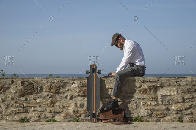 Man sitting on a wall in front of the sea working on laptop