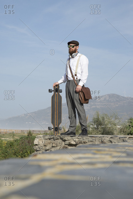 Bearded man standing on a wall with laptop- long board and leather bag