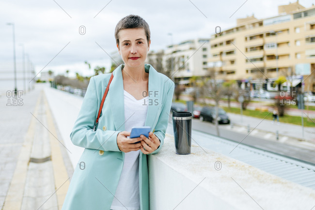 Woman dressed in jacket suit with smartphone and thermo mug