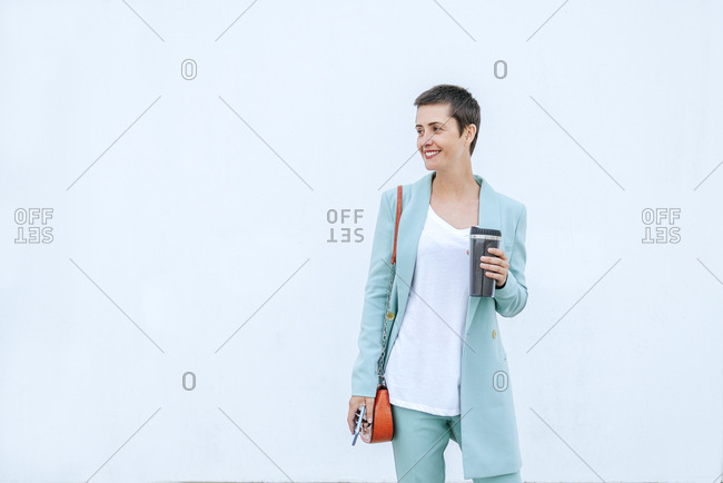 Woman in suit jacket holding thermo mug and mobile phone- white background