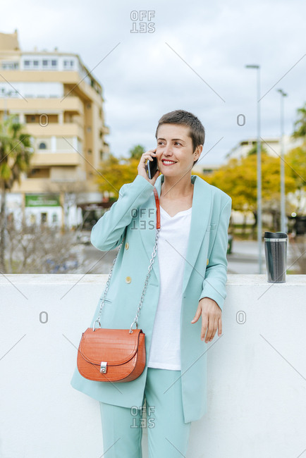 Woman dressed in jacket suit using smartphone- with thermo mug