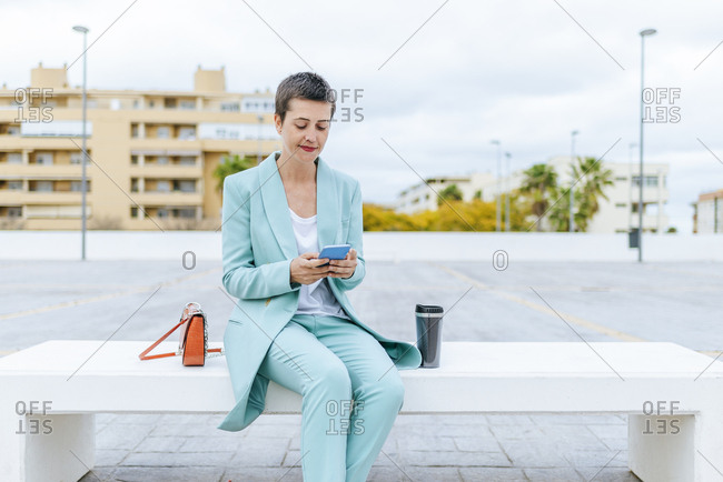 Woman in suit jacket sitting on bench using mobile phone