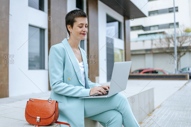 Woman in suit jacket using laptop outdoors
