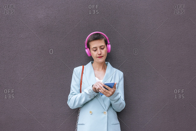 Woman dressed in jacket listening to music with her mobile phone