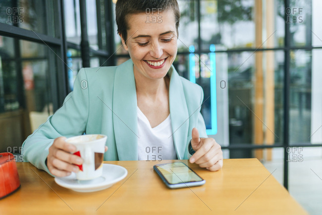 Woman in bar with mobile phone and coffee cup