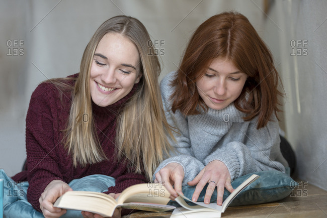 Two friends lying side by side on the floor reading books