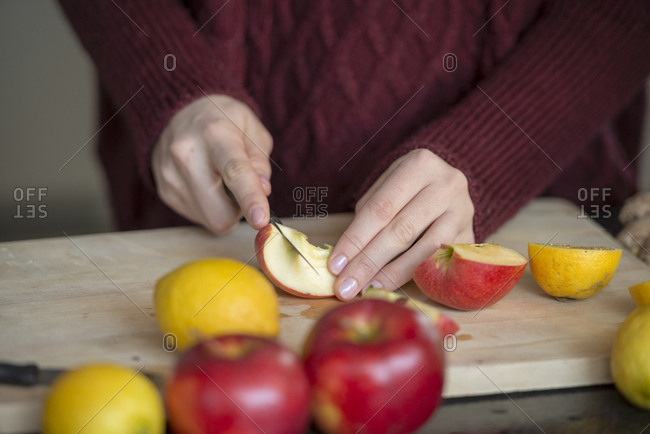 Hands of young woman cutting fruits on wooden board- close-up