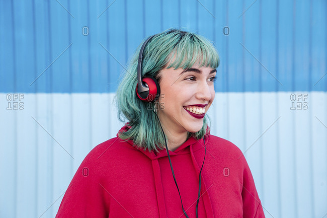 Portrait of laughing young woman with blue dyed hair listening music with headphones