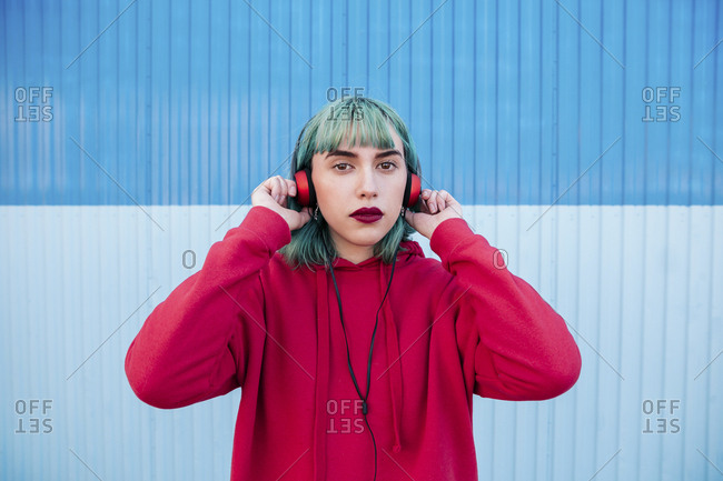Portrait of young woman with blue dyed hair listening music with headphones