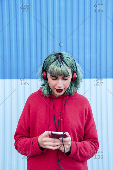 Portrait of young woman with blue dyed hair listening music with headphones looking at smartphone