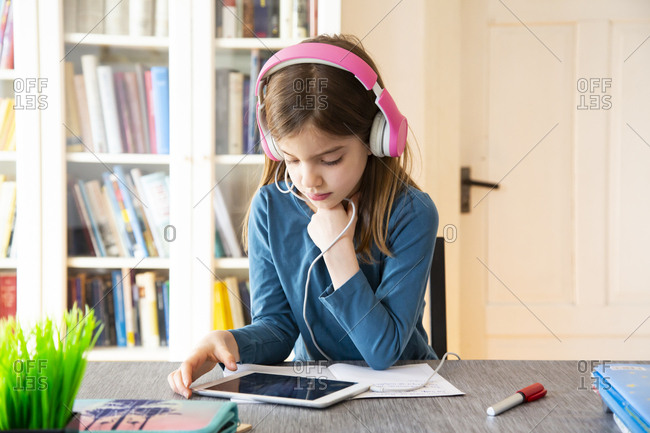 Little girl doing homework with headphones and digital tablet