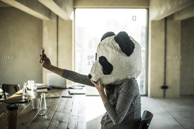 Woman with panda mask sitting in office- taking selfie