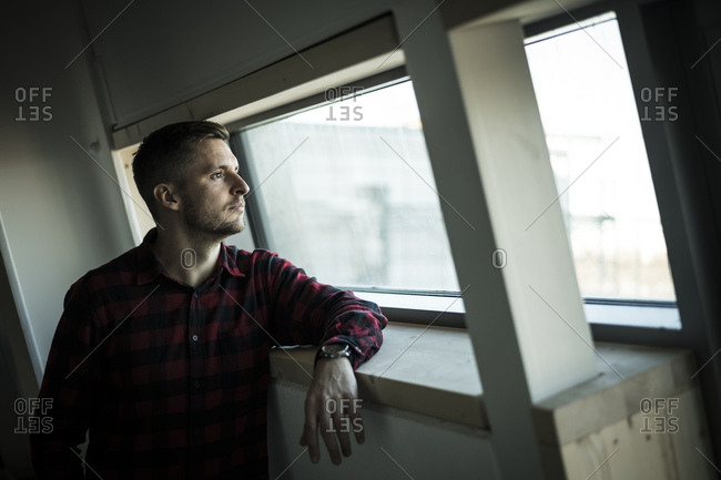 Young man looking out of window- daydreaming