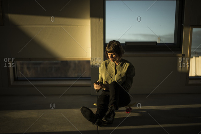 Businesswoman sitting on office floor at sunset- using smartphone