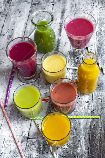 Different colorful smoothies in glasses and bottles