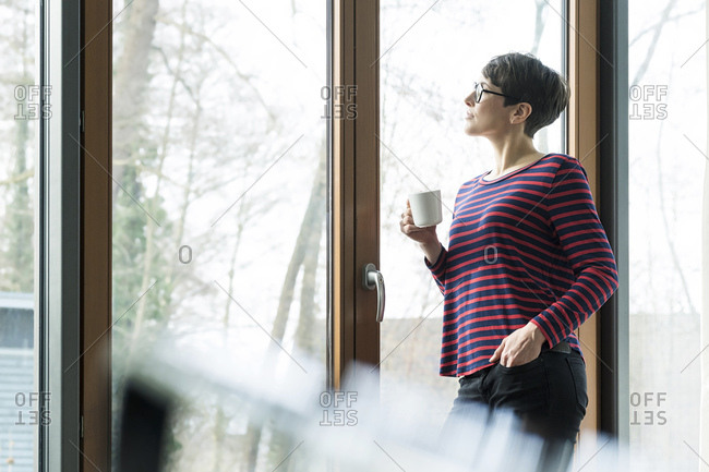 Woman with coffee mug looking out of terrace door