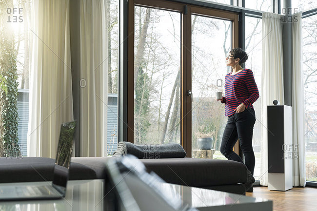 Woman with coffee mug standing in the living room looking out of terrace door