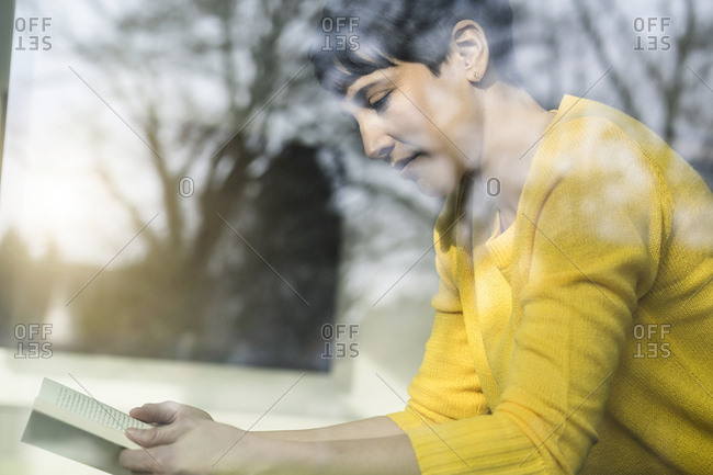 Woman sitting behind windowpane  reading book
