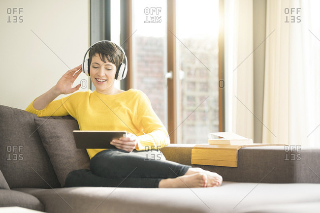 Portrait of happy woman sitting on the couch at home listening music with headphones while looking at tablet