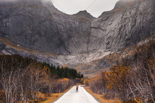 Norway- Lofoten Islands- man standing on empty road surrounded by rock face